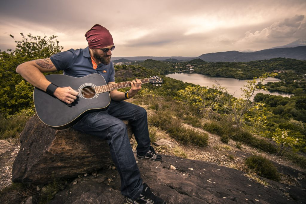 Man playing guitar outside sitting on a rock